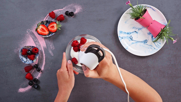 skyr and raspberries blended together in glass bowl dessert ideas for party grey surface with berries on it