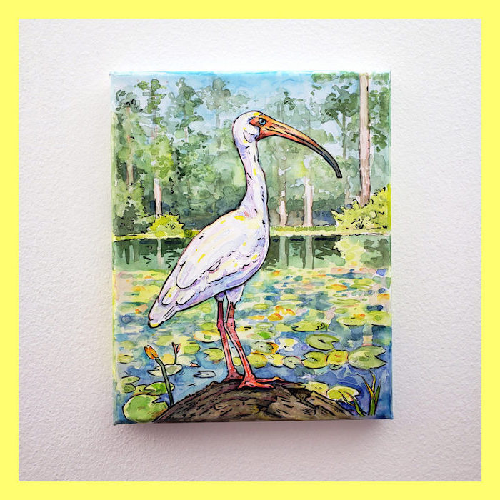 stork standing on a rock, lake with lillies, how to use watercolor, tall green trees in the background