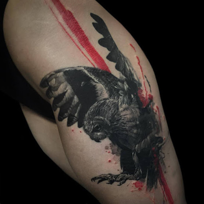 thigh tattoo of large black owl realistic trash polka style tattoo his wings spread wide red lines going across