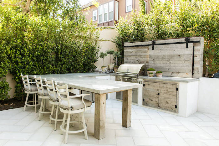 tiled floor in white l shaped outdoor kitchen wooden cabinets backsplash granite countertops wooden chairs
