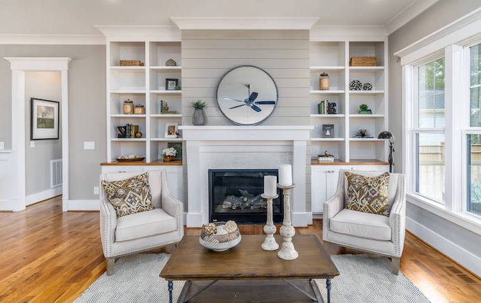 white carpet on wooden floor, modern farmhouse interior, two white armchairs, wooden coffee table, placed in front of a fireplace