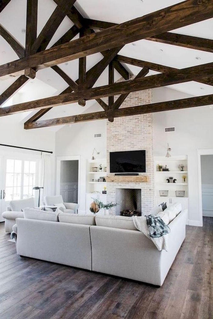 exposed wooden beams on white ceiling, farmhouse living room furniture, white furniture set, placed in front of a fireplace