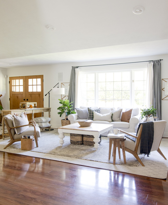 white carpet on wooden floor, industrial farmhouse decor, white sofa with throw pillows, grey armchairs, wooden coffee table