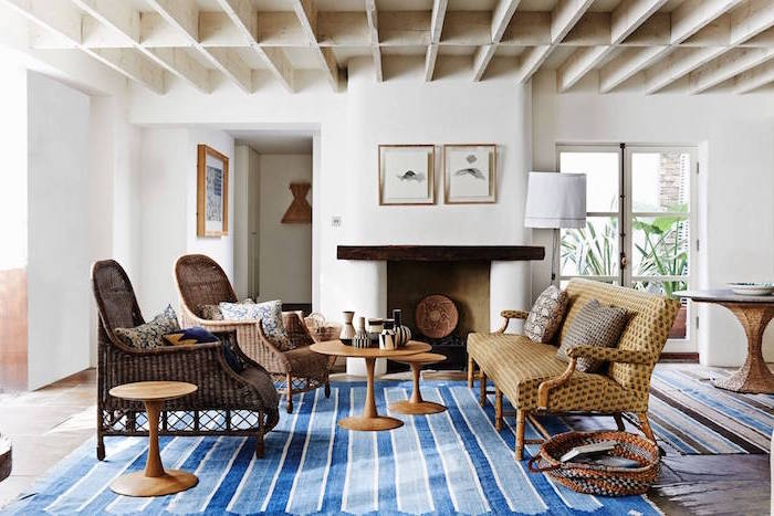 blue carpet on wooden floor, farmhouse chic decor, ratan furniture set, placed in front of a fireplace
