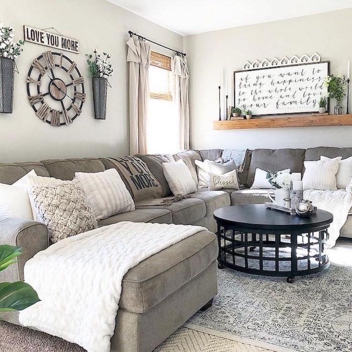 grey corner sofa, farmhouse chic decor, black round coffee table, lots of throw pillows