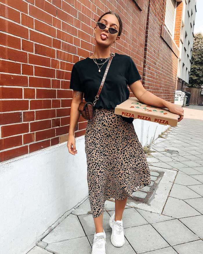 woman carrying box of pizza wearing leopard print skirt black t shirt white sneakers sunglasses cute casual outfits small leather bag