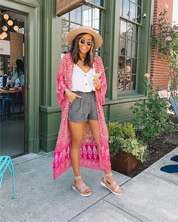 woman wearing dark grey shorts white top long pink kimono cute trendy outfits pink sandals and hat