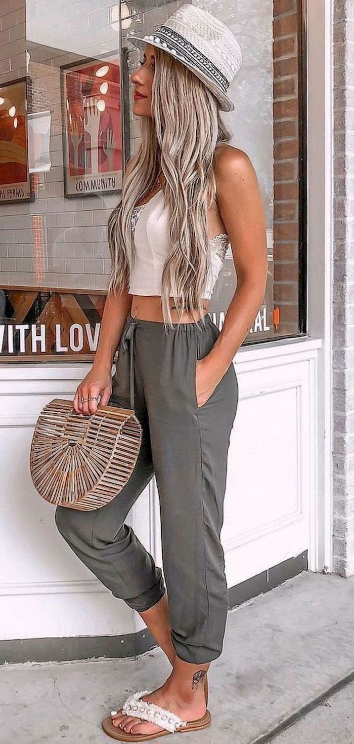 woman wearing dark grey wide fit trousers cute outfit ideas white lace crop top hat bag sandals