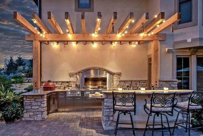 wooden beams with strings of light modern outdoor kitchen grill and metal cabinets kitchen island made of stone black metal bar stools