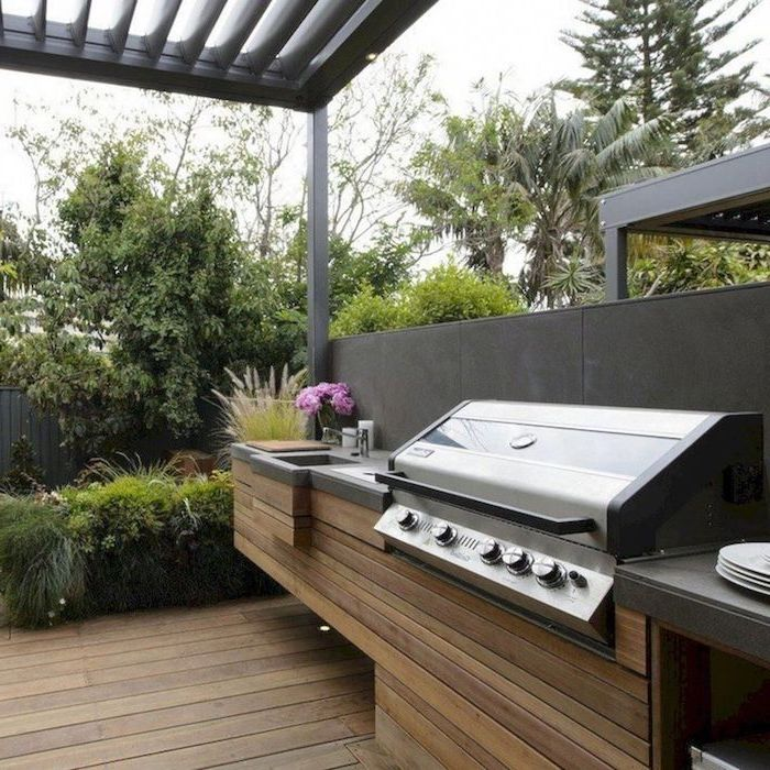 wooden cabiners under the grill grey countertop wooden floor backyard kitchen ideas surrounded by trees and bushes