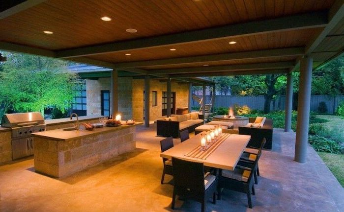 wooden ceiling backyard kitchen kitchen island made of stones outside lounge are with fireplace and sofas