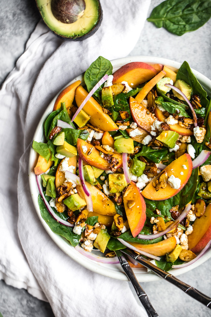 avocado peach spinach onion walnuts crumbled feta cheese in white bowl with two spoons on the side dinner salad recipes