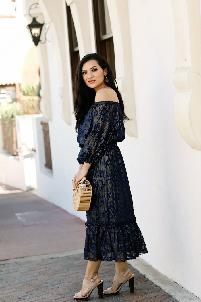 beach wedding guest dresses woman with long black hair wearing black strapless dress with navy blue decorations nude sandals