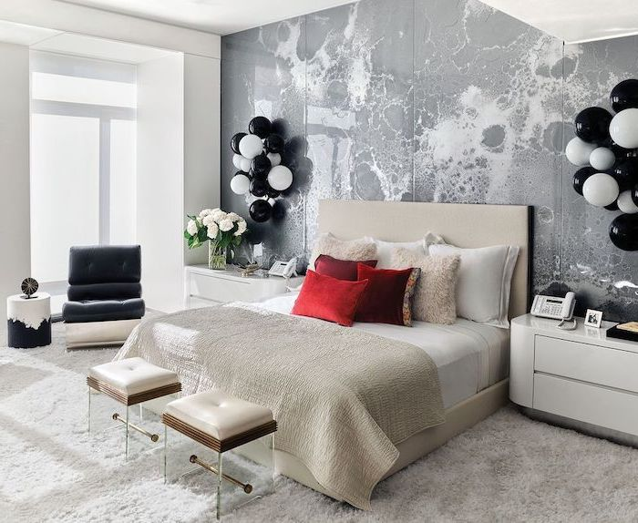 bedroom wall decor ideas grey accent wall behind bed with white bed frame red throw pillows two ottomans in front of the bed