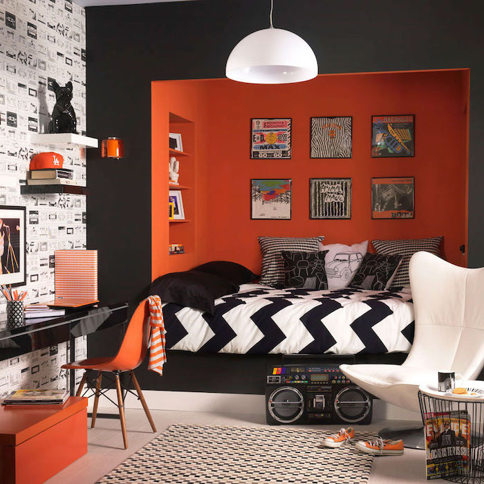 black and orange walls bedroom ideas for teenage guys with small rooms bed nook colorful posters hanging above the bed black desk with orange chair
