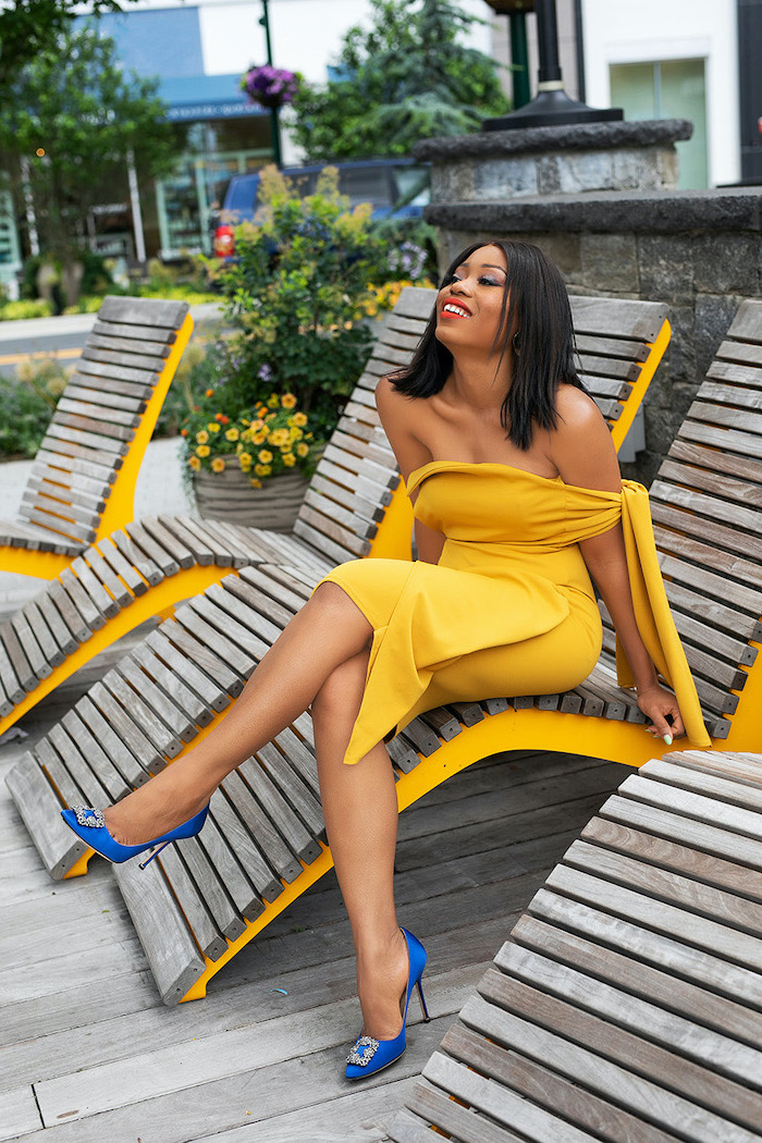 black haired woman wearing yellow strapless dress blue satin shoes cocktail dresses for weddings sitting on wooden lounge chair