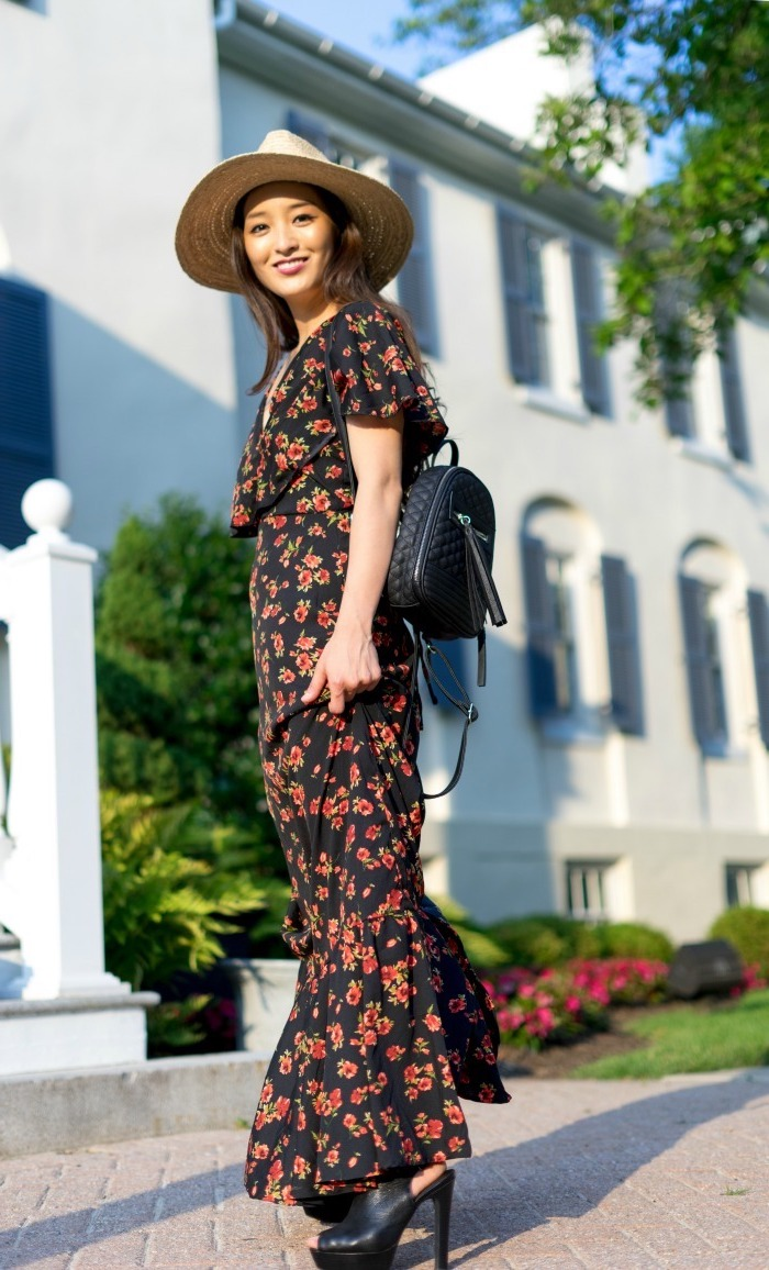 black long dress with red flowers worn by brunette woman long summer dresses black leather shoes and backpack