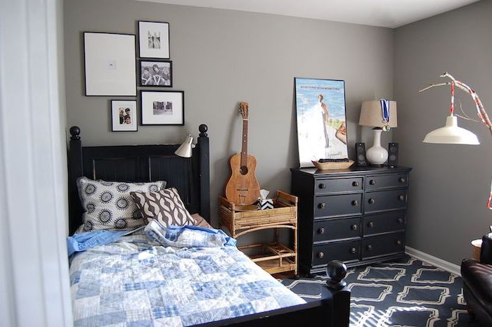 black wooden bed frame and drawers teen boy bedroom furniture grey walls framed photos above the bed guitar on the night stand