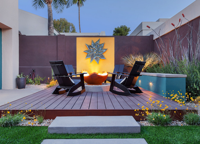 black wooden lounge chairs arranged around fire pit on wooden floor concrete patio ideas lots of plants