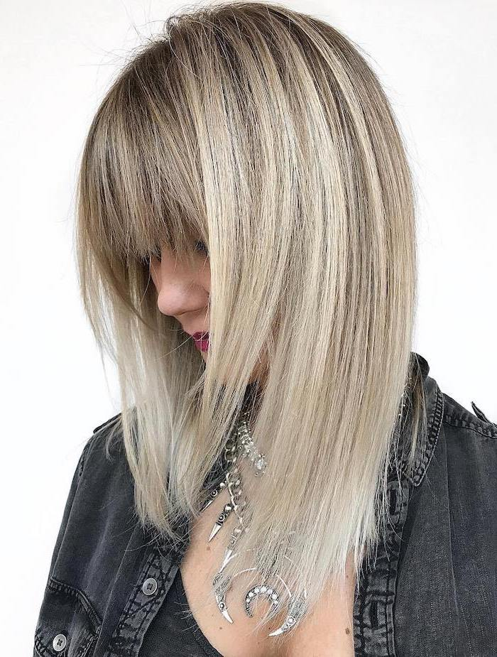 blonde hair with bangs and blonde highlights hairstyles for medium hair woman wearing black denim shirt lots of silver necklaces