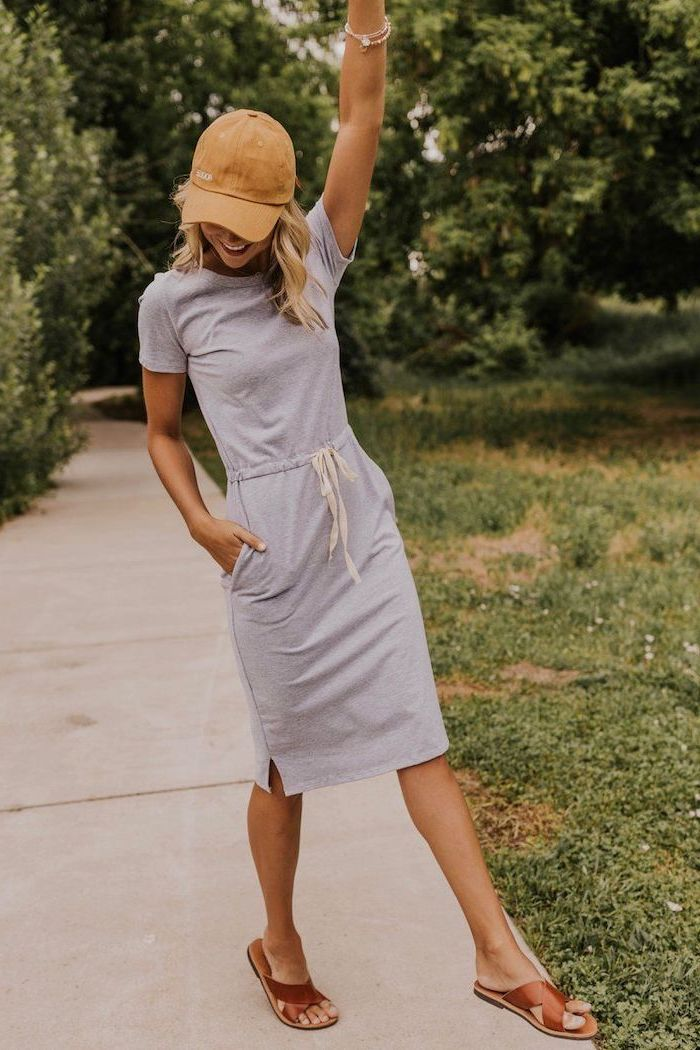 blonde woman wearing grey t shirt dress casual summer dresses brown leather sandals brown baseball cap