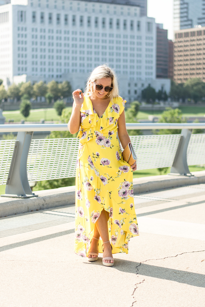 blonde woman wearing long yellow wrap around dress with purple flowers long sleeve wedding guest dresses nude sandals