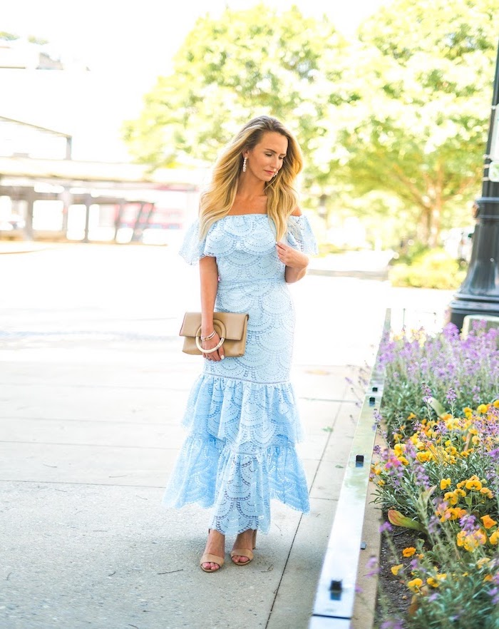 blonde woman with long wavy hair beautiful dresses to wear to a wedding wearing blue lace strapless dress nude sandals leather bag