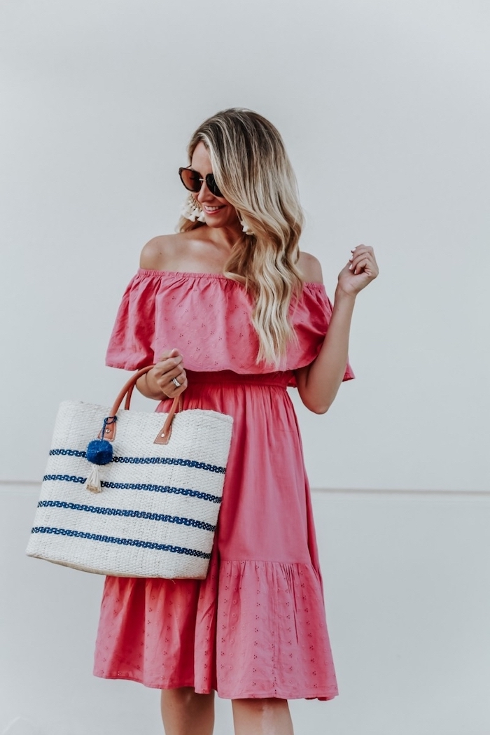 blonde woman with long wavy hair wearing pink strapless dress white bag summer beach dresses