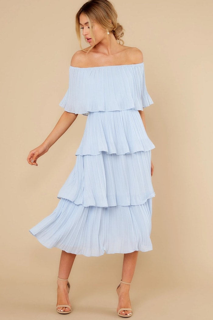 blonde woman with low updo cocktail dresses for weddings wearing strapless blue pleated midi dress nude sandals