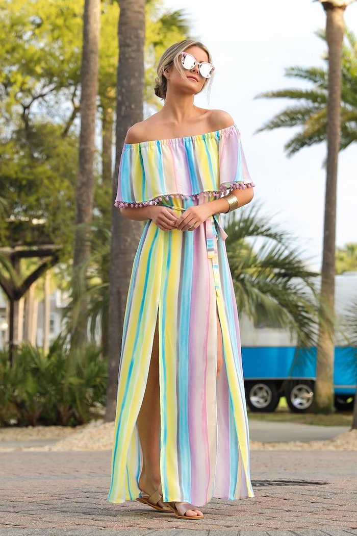 blonde woman with low updo wearing sunglasses womens dresses long dress in pink blue and yellow bare shoulders