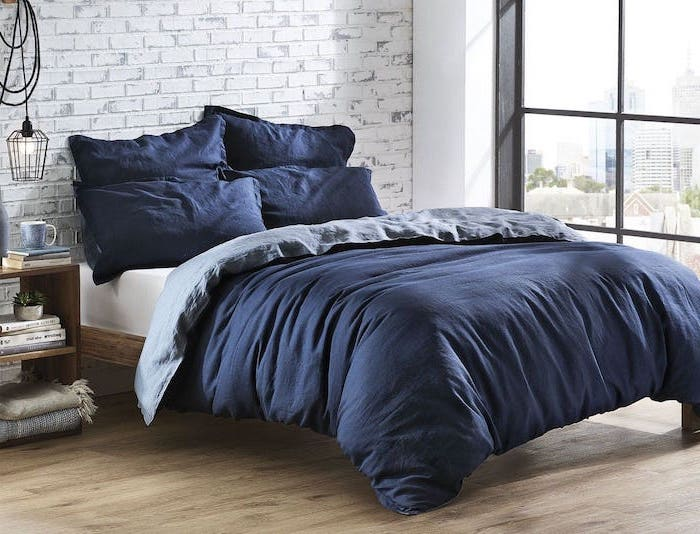 blue bed sheets on wooden bed frame bedroom ideas for teenage guys with small rooms brick wall behind it wooden floor