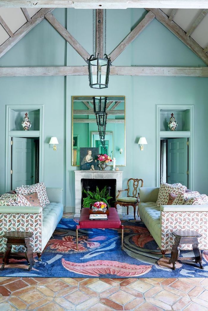 blue carpet on tiled floor neutral color palette mint green walls cathedral ceiling with exposed wood beams mint green sofas in front of fireplace