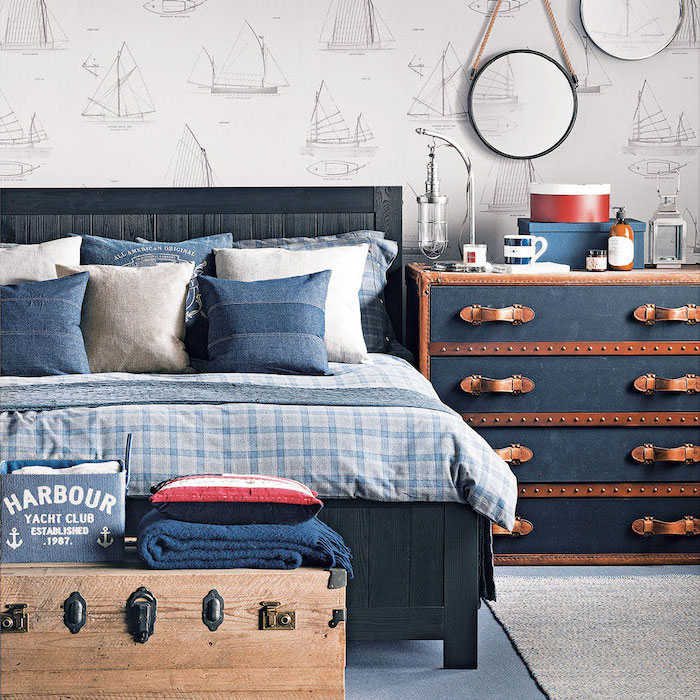 blue throw pillows bed sheets on bed with black wooden frame teen boy bedroom furniture nautical themed room with boats on white wall