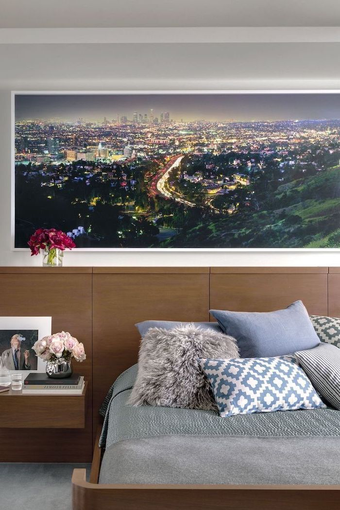 blue throw pillows on bed with wooden backboard bedroom decor ideas framed photo of big city skyline at night hanging above the bed