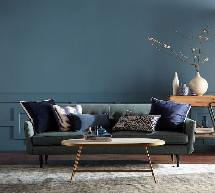 blue wall living room color schemes grey sofa with navy blue throw pullows wooden floor side table brass coffee table
