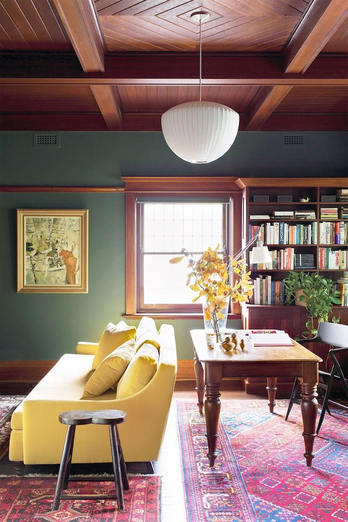 blue walls wooden ceiling floor living room wall colors yellow sofa wooden desk bookshelf colorful carpets