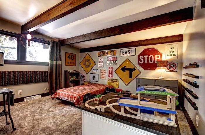 boys bedroom ideas expsoed wooden beams on white ceiling large grey carpet different road signs on the wall behind the bed
