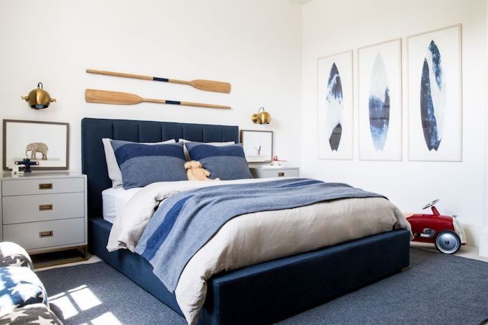 boys room paint ideas sailing theme two paddles hanging above dark blue velvet bed with white and blue bed sheets three posters on white wall