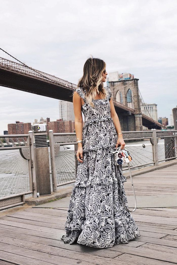 brooklyn bridge in the background flowy dresses brunette woman wearing lonf black and white printed dress standing on the pier