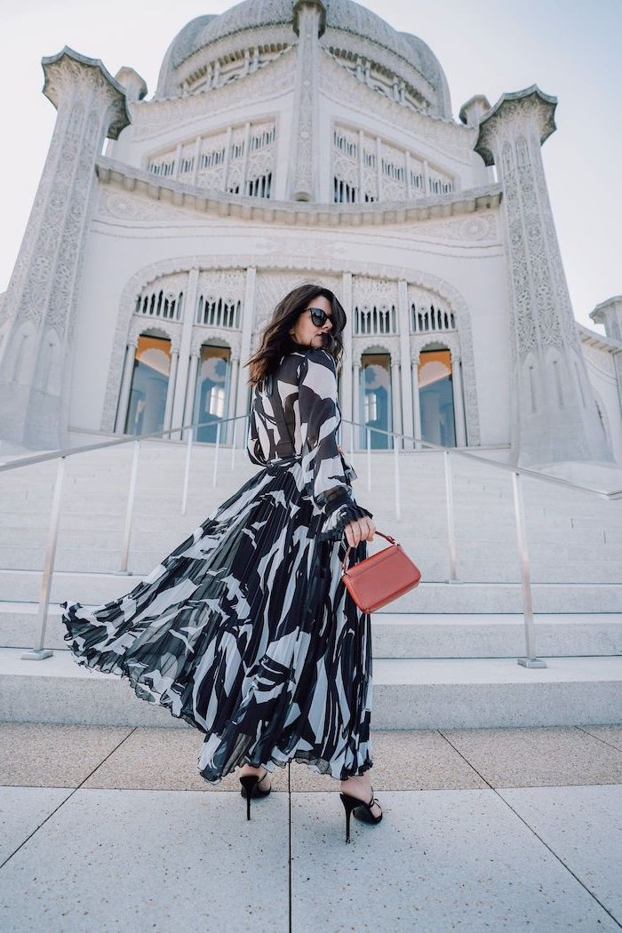 brunette woman wearing long black and white dress summer wedding guest dresses black sandals brown leather bag standing in front of church