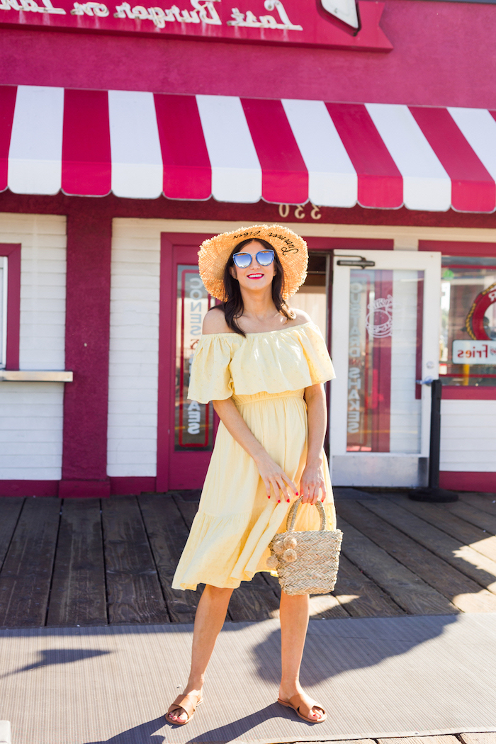 brunette woman wearing yellow strapless dress straw hat sunglasses brown leather sandals white summer maxi dress