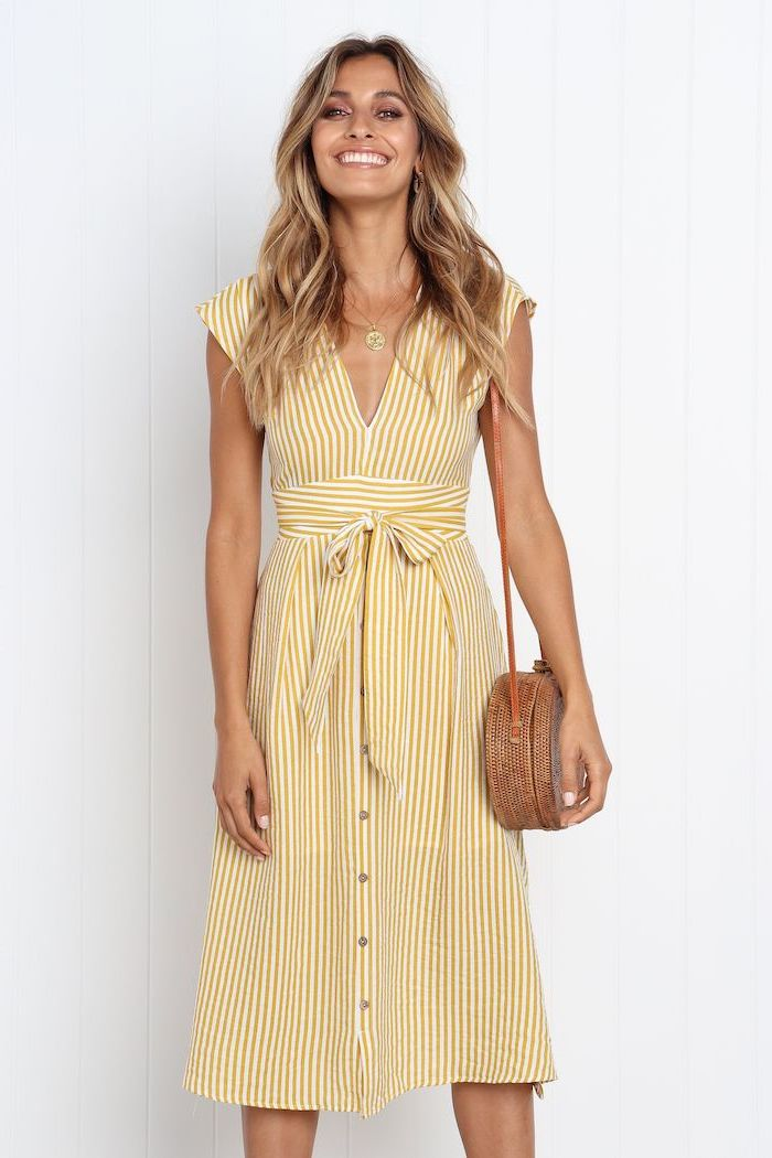 casual summer dresses woman with long blonde wavy hair wearing white dress with yellow stripes brown bag