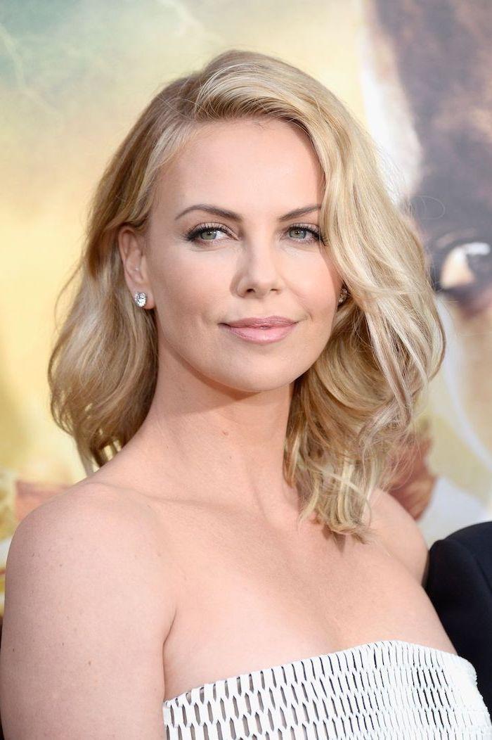 charlize theron wearing white strapless dress hairstyles for medium hair blonde wavy hair diamond earrings