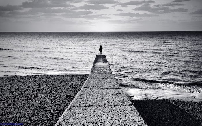 cool wallpaper hd black and white photo of man standing at the end of pier looking at the ocean