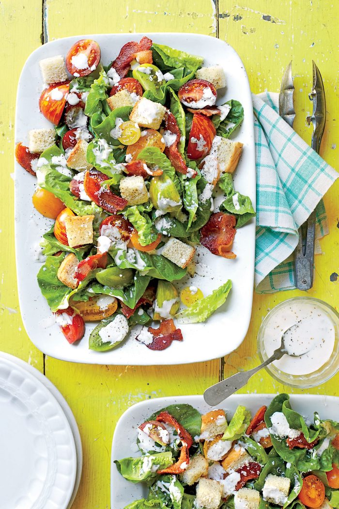 croutons prosciutto halved cherry tomatoes green salad with dressing summer salads white plate on yellow wooden surface