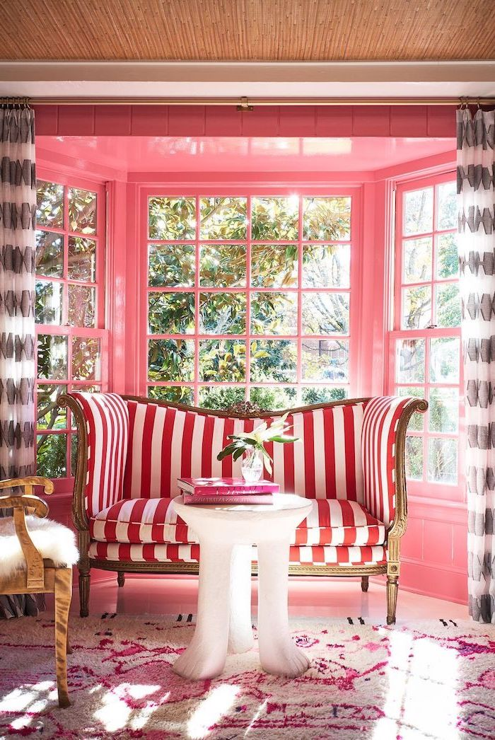 curtains in black and white neutral color palette walls painted in pink red and white striped sofa white coffee table