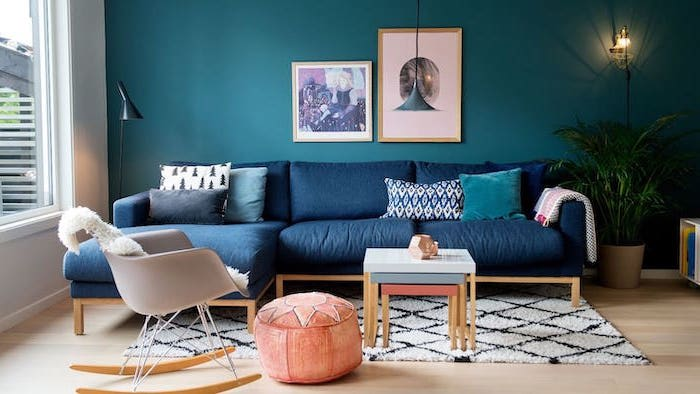 dark blue corner sofa turquoise wall with wall art interior paint colors white and black carpet on wooden floor orange ottoman