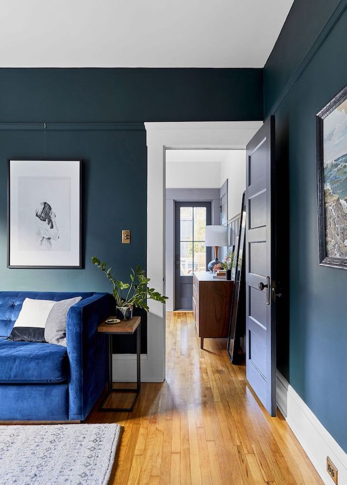 dark blue walls wooden floor with grey carpet living room paint color ideas blue velvet sofa wall art