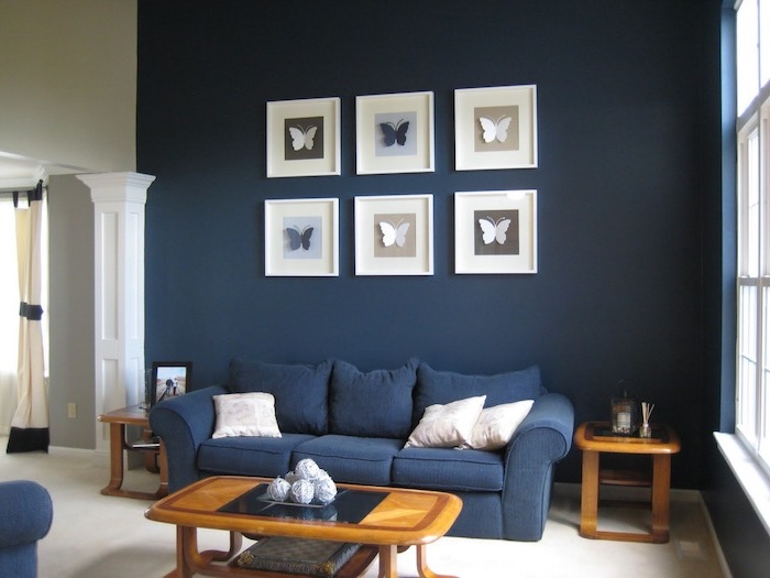 dark navy blue walls with paper butterflies wall art interior paint colors navy blue sofa wooden coffee table and side tables