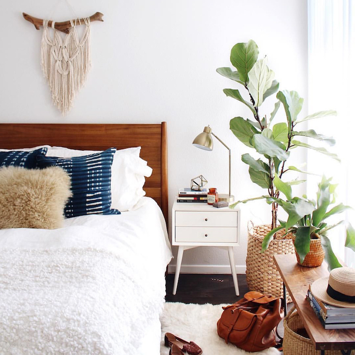 dark wooden floor with white carpet white bed sheets on bed with wooden bed frame blue throw pillows potted plants